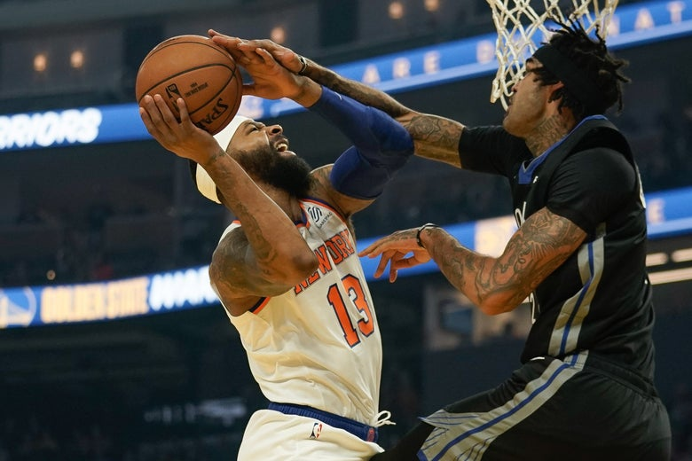Knick Marcus Morris grimacing as he gets stuffed (and fouled) on a layup against the Warriors' Willie Cauley-Stein