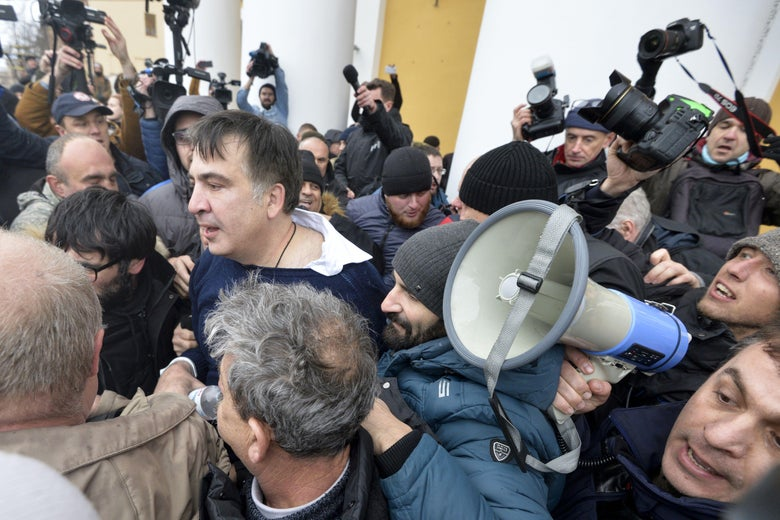 TOPSHOT - Former Georgian Mikheil Saakashvili (C-L) is seen after he was released by his supporters in downtown Kiev on December 5, 2017. Ukrainian security services on December 5 arrested former Georgian president Mikheil Saakashvili after he climbed onto the roof of his apartment building and addressed supporters during a police raid. The Ukrainian Security Service (SBU) said Saakashvili had been arrested on charges of assisting criminal organisations. / AFP PHOTO / Sergei CHUZAVKOV        (Photo credit should read SERGEI CHUZAVKOV/AFP/Getty Images)