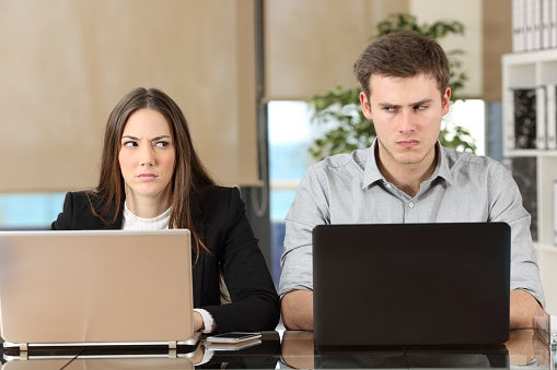 A woman and a man sit next to each other with laptops in front of them, looking annoyed and shifty-eyed.