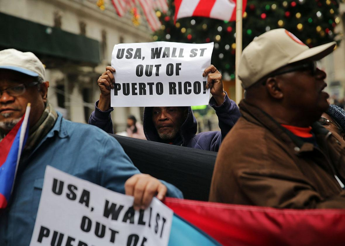 People protest outside of Wall Street against cutbacks and austerity measures forced onto the severely indebted island of Puerto Rico on December 2, 2015 in New York City.