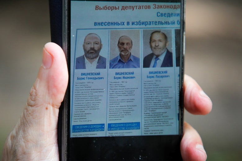 A cell phone showing the election website of three images of similar looking men all named Boris Vishnevsky.