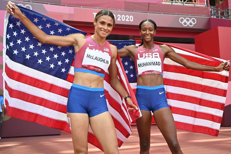 McLaughlin and Muhammad smile and drape American flags behind them on the track