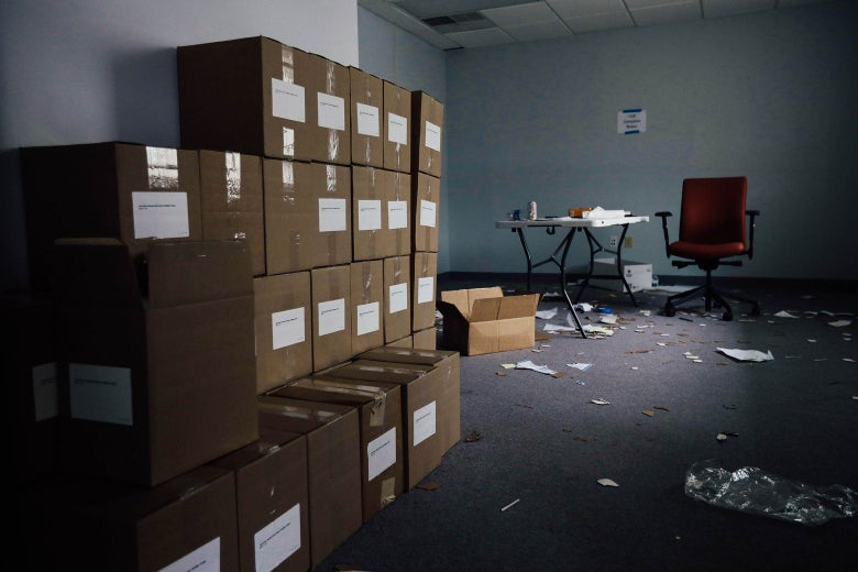Boxes are stacked in room. In the back, a desk and chair stand, with pieces of paper scattered around.