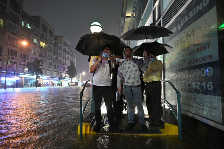 People holding umbrellas stand huddled at a subway entrance as water fills the street and sidewalk.