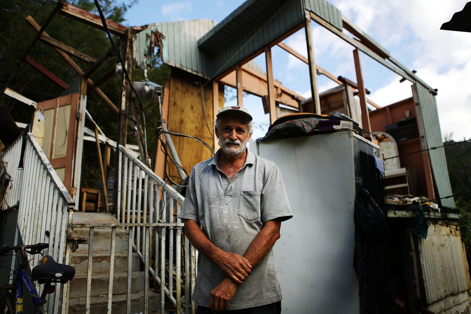 An older man stands in front of his destroyed home.