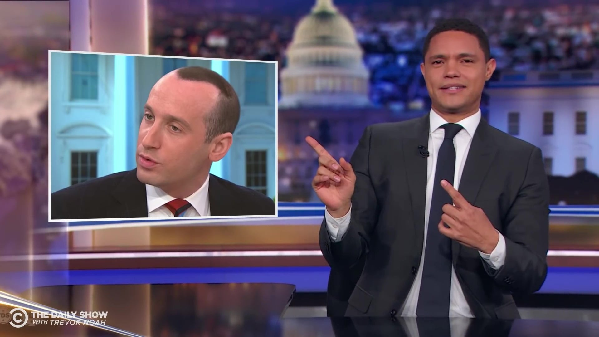 Trevor Noah, looking in confusion at a picture of Stephen Miller's strange hairstyle.