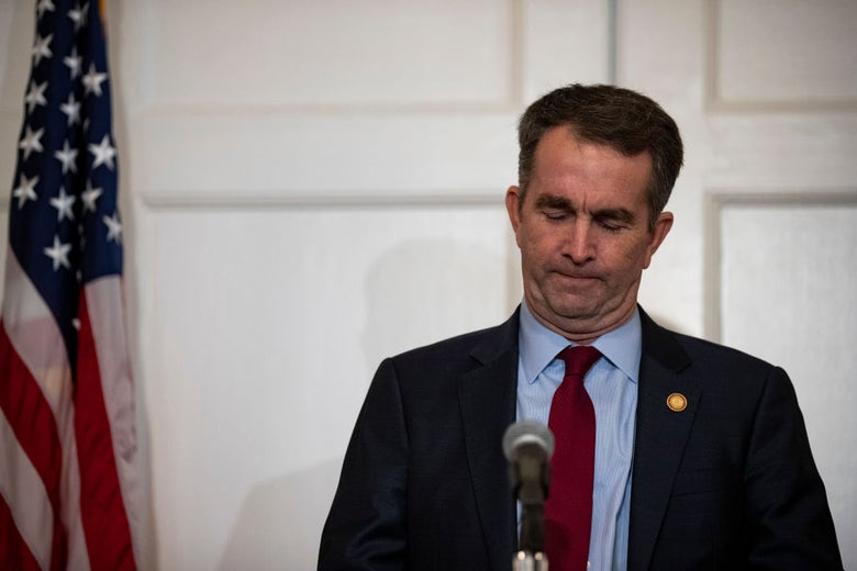 Northam, standing in front of an American flag on a flagpole, looks downward.