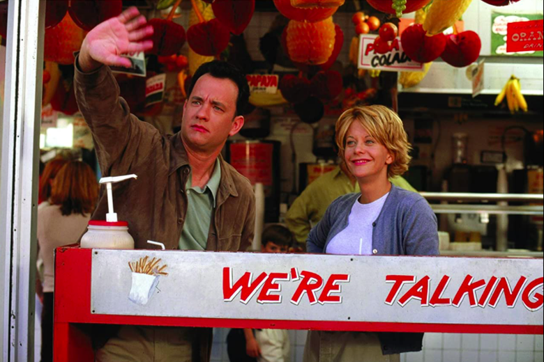Tom Hanks waves to someone off camera as Meg Ryan stands smiling next to him.