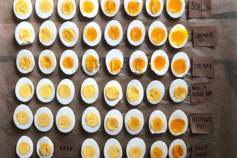 Dozens of halved, hard-boiled eggs lined up on a table. The egg yolks range from yellow and stiff to orange and runny.