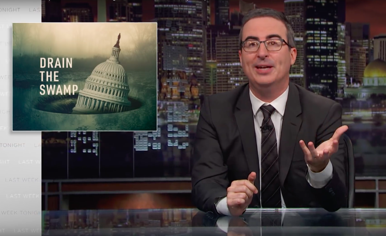 """Last Week Tonight's John Oliver in front of a graphic reading """"Drain the Swamp."""""""