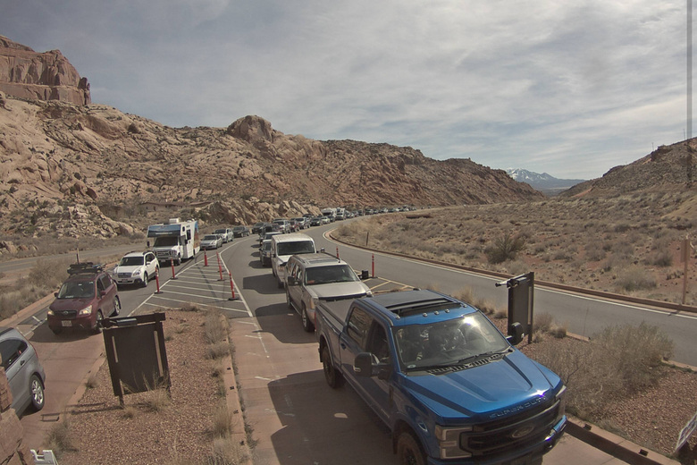 A long line of cars waits to get in to Arches National Park.