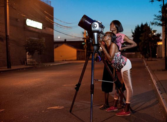 two women observe Saturn