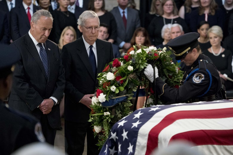 Chuck Schumer and Mitch McConnell stand solemnly in front of a wreath being placed by an official by McCain's casket.