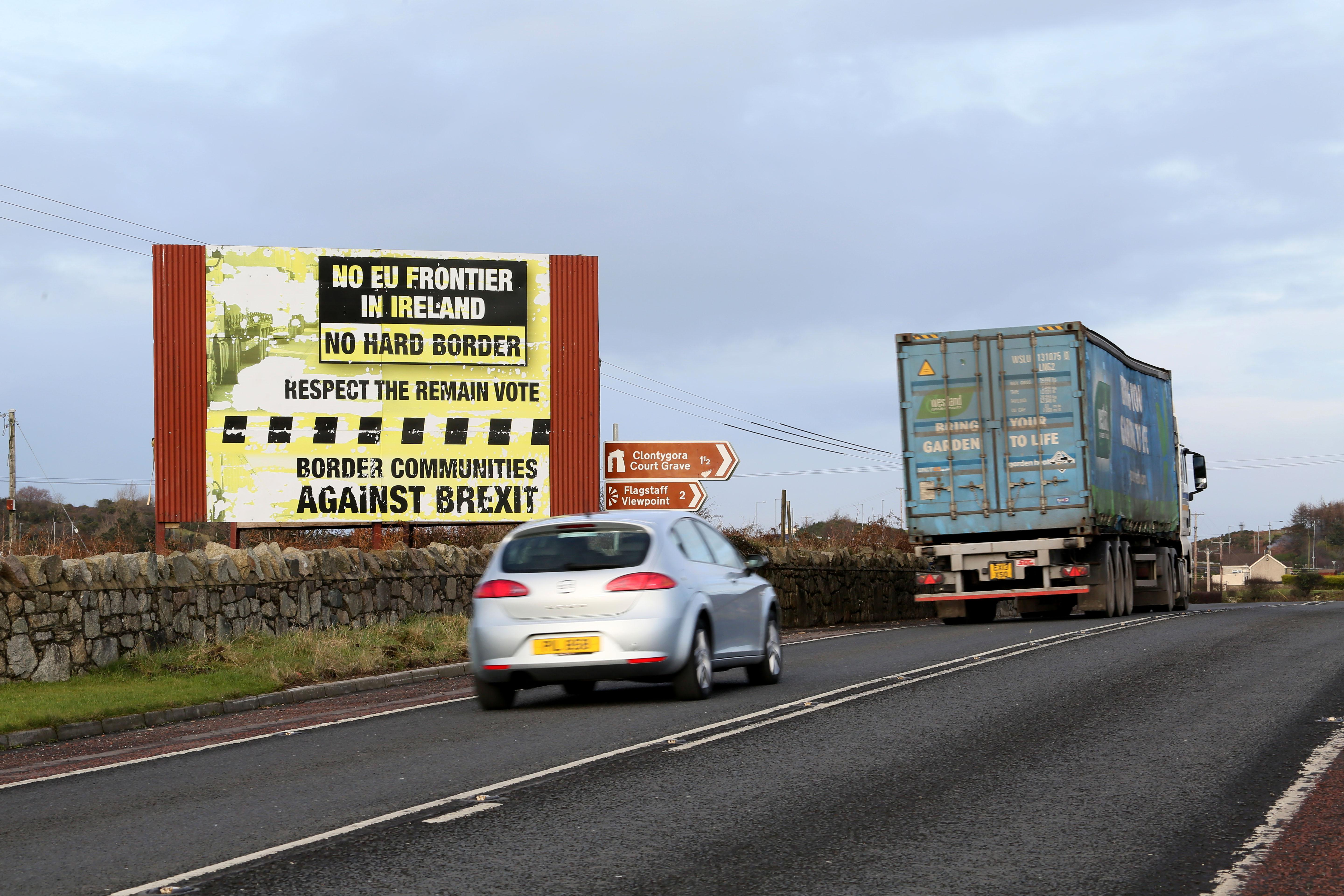 Traffic passes a Brexit Border poster on the Dublin road Co Armagh border, between Newry in Northern Ireland and Dundalk in the Irish Republic, on December 1, 2017,           The European Union will not accept Britain's  Brexit offer if Ireland is not satisfied with proposals for future border arrangements, EU President Donald Tusk said in Dublin on December 1, 2017. / AFP PHOTO / Paul FAITH        (Photo credit should read PAUL FAITH/AFP/Getty Images)