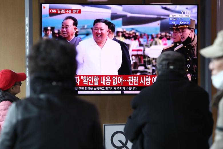 People watch a TV screen showing Kim Jong-un
