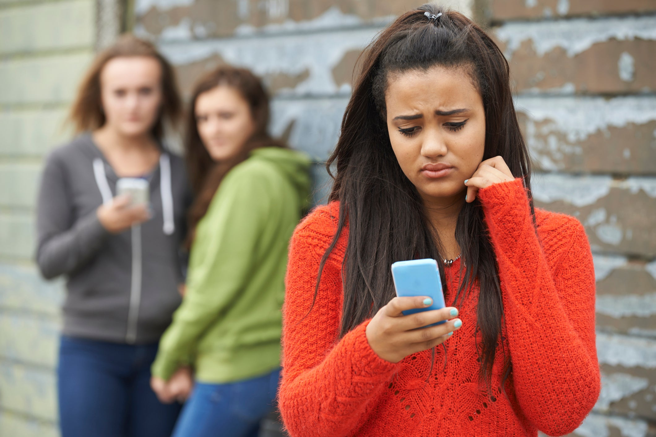 A teen girl looking sad at her phone because of cyberbullying.