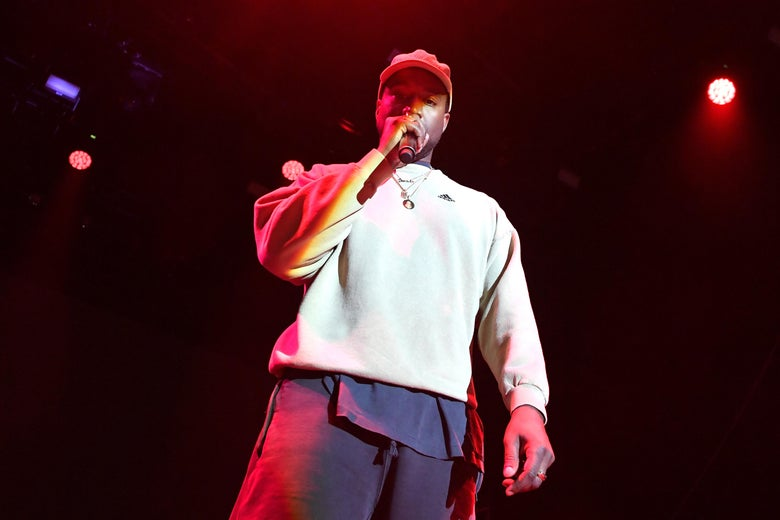 Kanye West holds a microphone onstage.