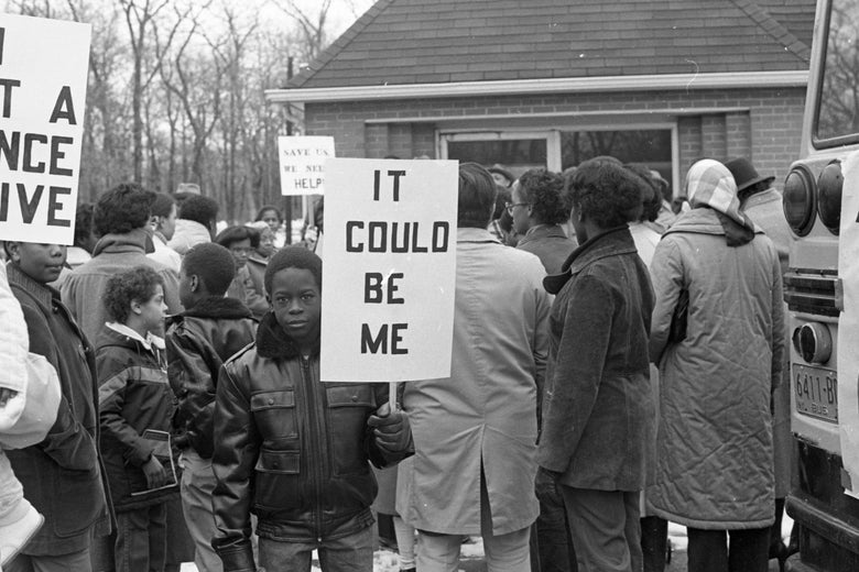 "A black-and-white photo shows a black child carrying a serious expression and a sign that reads ""It could be me."" He is standing facing away from a crowd that is staring at a house."