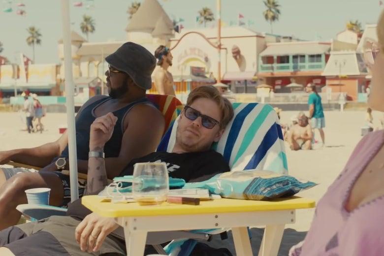 Tim Heidecker, sitting in a beach chair.
