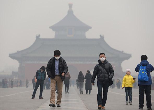 People wearing masks walk on Danbi Bridge at the Temple of Heaven Park Beijing, China.