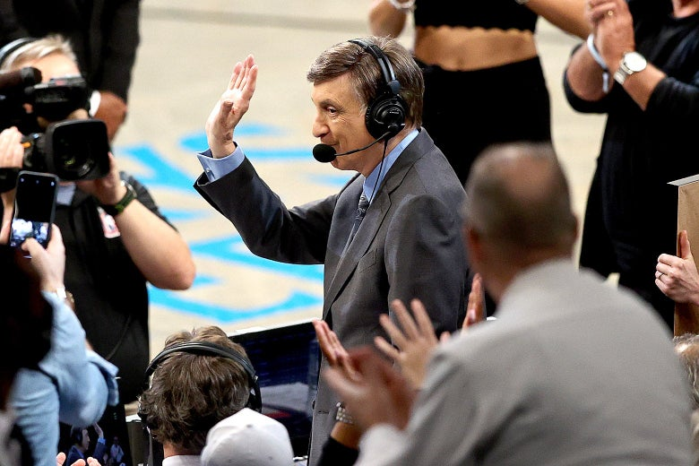 Marv Albert standing with headset on courtside, as the crowd cheers