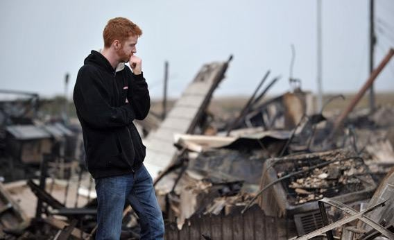 Gavin Byrne views damage in the Breezy Point area of Queens in New York on October 30, 2012 after fire destroyed about 80 homes as a result of Hurricane Sandy.