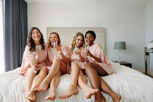 Stock art of four young women smiling and laughing while sitting on a hotel bed in matching robes, holding glasses of champagne.