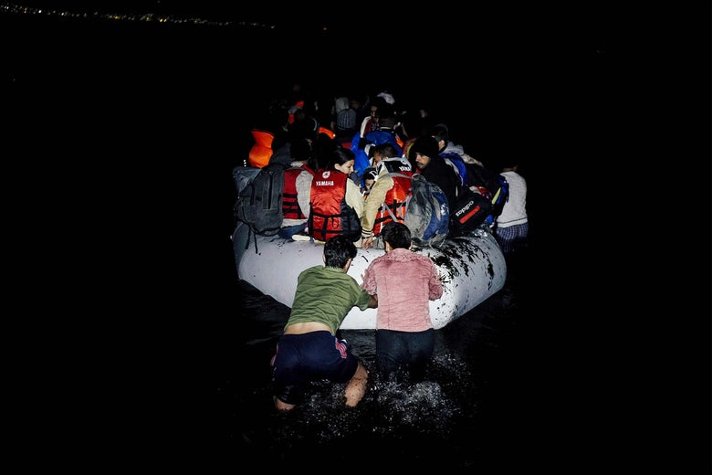 Refugees on a dinghy in the dark.