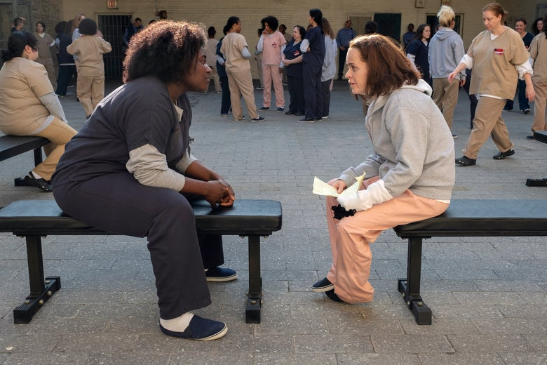 Danielle Brooks and Taryn Manning sit on separate benches in a prison yard, facing each other.