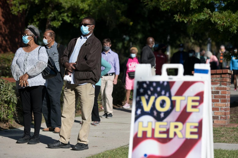 "A group of voters wearing masks waits outside a polling place. A ""Vote Here"" sign can be seen."