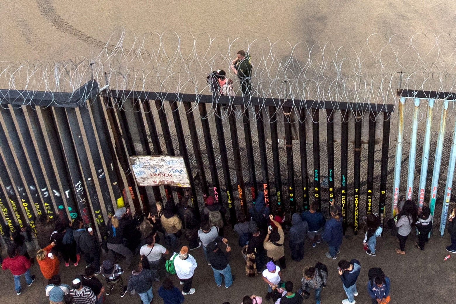 Aerial view of migrants standing at the border fence.