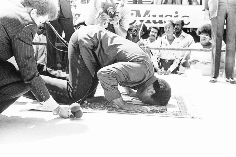 A kneeling Ali rests his head on a prayer mat in a boxing ring while surrounded by press.