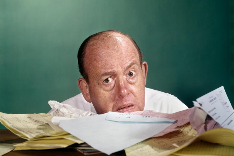 Image of a middle-aged man peering out from behind a large, messy stack of paperwork.