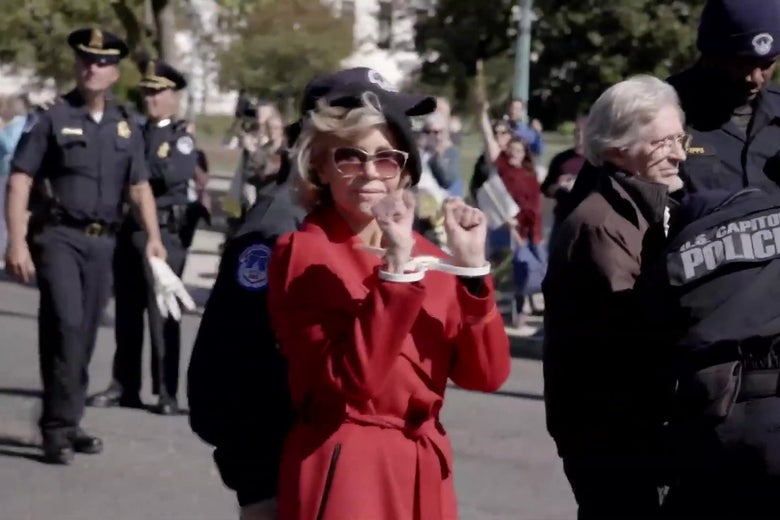 Jane Fonda holding her zip tied hands in front of her at a climate protest.