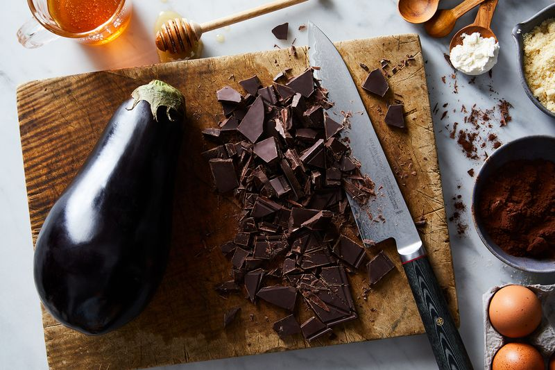 A large dark purple eggplant, a kitchen knife and lots of fragments of chocolate sit on a cutting board next to other cooking ingredients