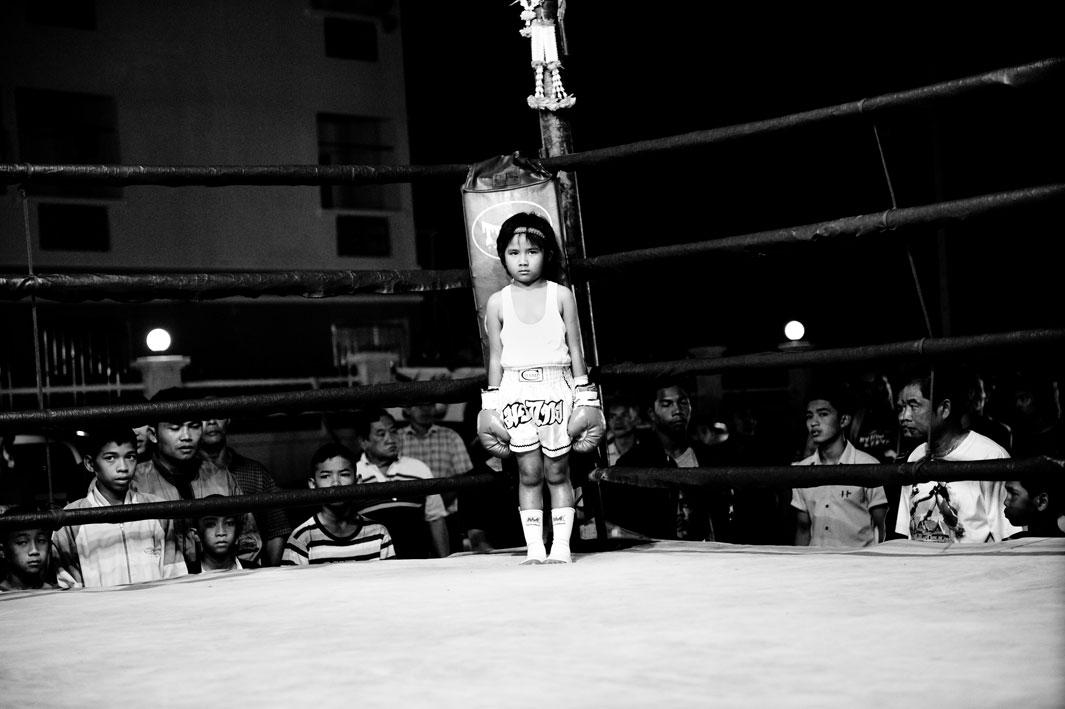 Girl, 6 years, in a boxing ring. Muay Thai (Thai Boxing) is one of the toughest martial arts in the world. A minimum age for the fighters does not exist. For many poor people it secures their livelihood. For a pittance, they reach their mental and physical limits two or three times a month with boxing matches.