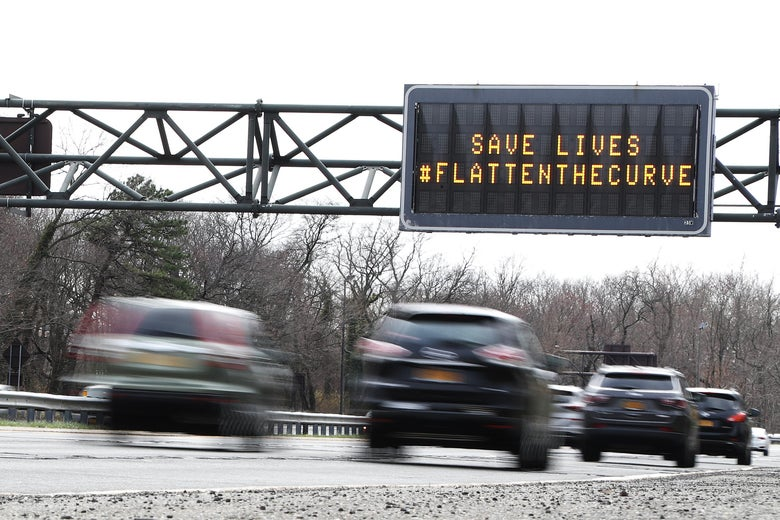 "A sign reading ""Save lives, flatten the curve"" over a highway."
