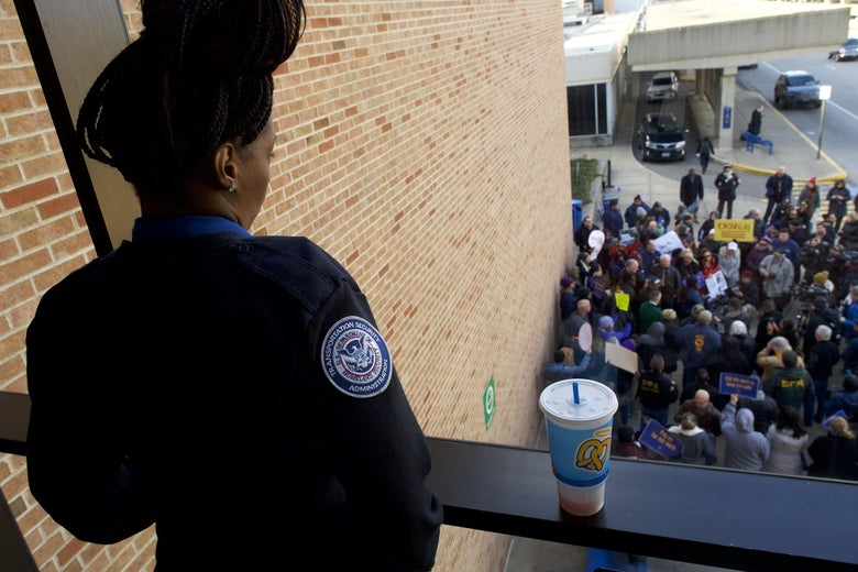 A TSA employee watches fellow TSA employees and other airport workers protest outside the Philadelphia International Airport.