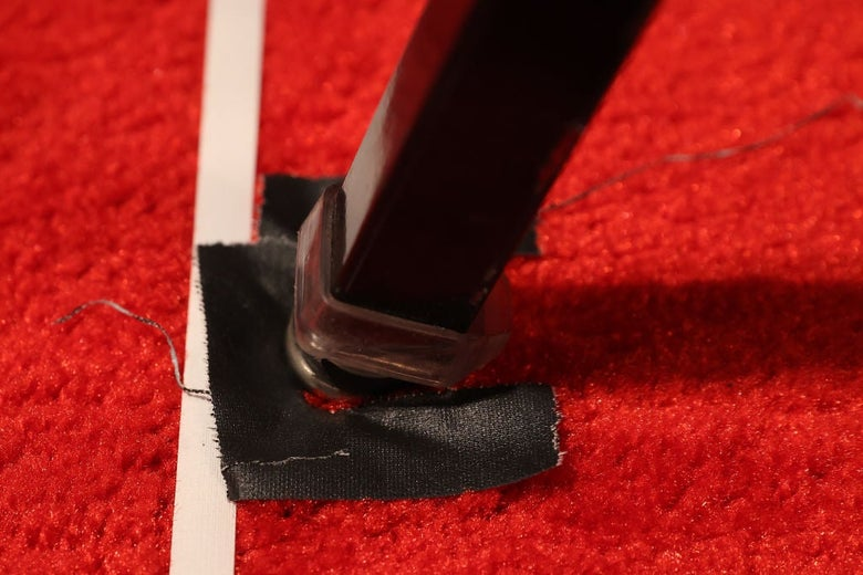 Close-up of a chair leg resting on a square of black tape next to a vertical strip of white tape on a red carpet.