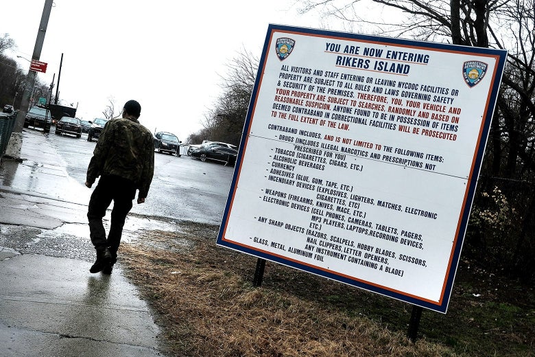 A man walks away with a sign about Rikers Island in the foreground.