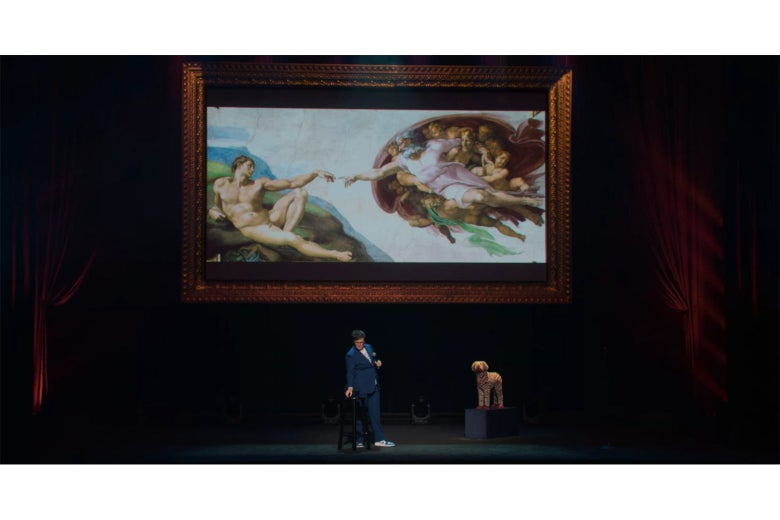 Hannah Gadsby onstage in front of a screen displaying Michelangelo's painting of God reaching out to touch Adam.