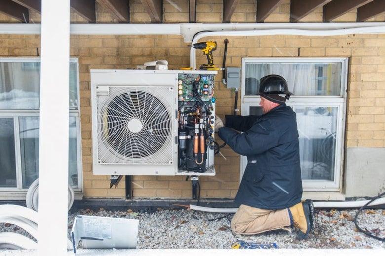 A worker installs a heat pump on an apartment building.