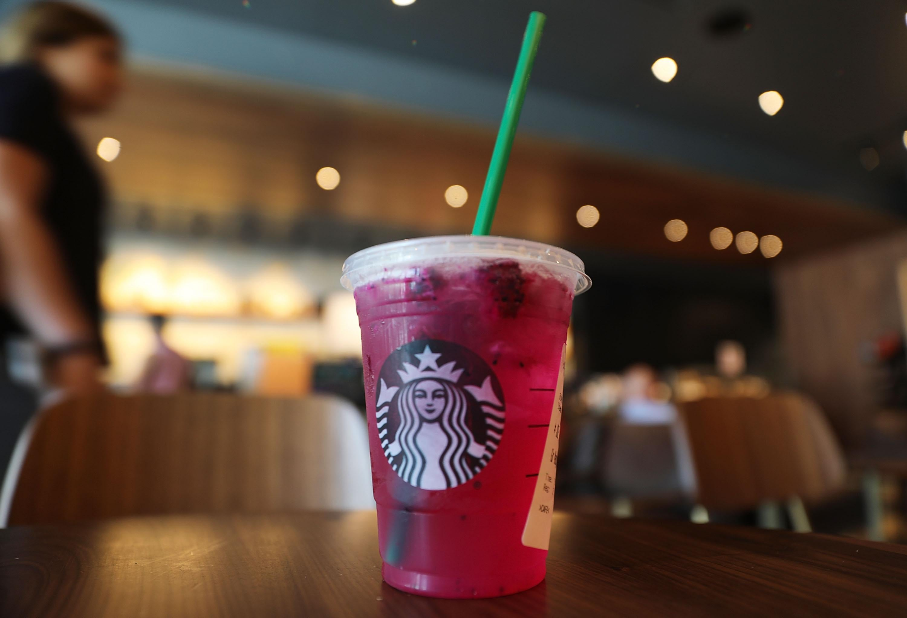 A plastic straw is seen in a pink Starbucks drink.