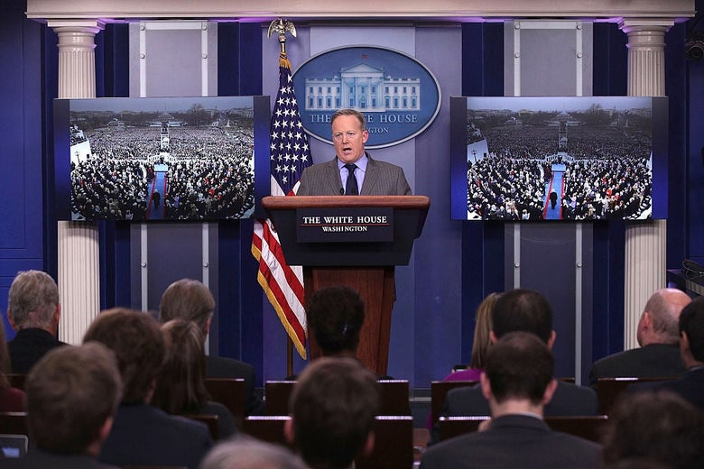 Sean Spicer speaks at the White House press room lectern while flanked by identical pictures of Trump's inauguration crowd taken from a flattering angle.