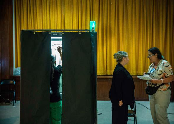 A woman votes at a polling station on September 10, 2013.