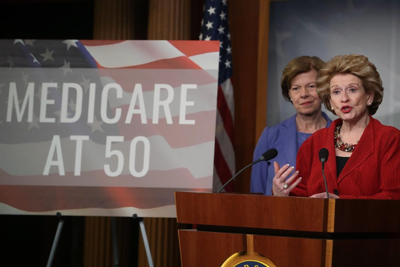 "Tammy Baldwin and Debbie Stabenow onstage next to a poster reading ""Medicare at 50."""