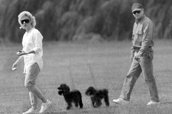 Whitey Bulger and Catherine Greig walk together with Greig's poodles underfoot, June 1988.