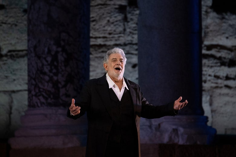 Placido Domingo stands alone on a stage, arms outstretched, mouth open.