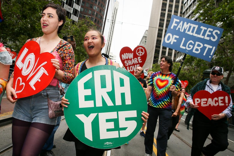 "A marcher holds an ""ERA YES"" sign amid others holding pro-LGBTQ signs in the pride parade."