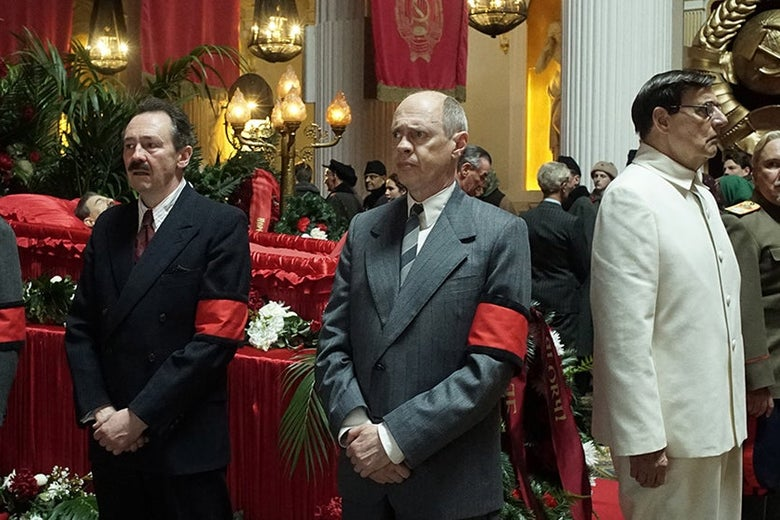 Dermot Crowley, Steve Buscemi, Jeffrey Tambor, and others stand around a casket.